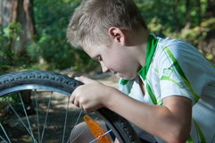 Boy repairing a bicycle wheel Royalty Free Stock Photography