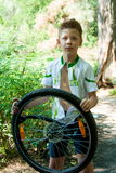 Boy repairing a bicycle wheel Stock Photos