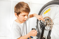 Boy repairing bike drawing up a bolt with spanner Stock Image