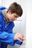 Boy repairing door on the outside. Royalty Free Stock Photos