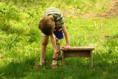 Boy repairing wooden bench with a hammer in the back yard. Outdoors Stock Photos