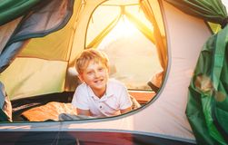 Boy rest in camping tent. Sunset time in nature stock photos