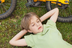 Boy resting besides bicycle at park Stock Images