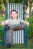 Boy is resting in a deckchair Royalty Free Stock Photography