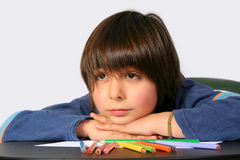 Boy resting on desk with colored pencils Stock Photo