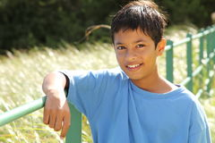 Boy resting on fence rail in countryside sunshine Royalty Free Stock Image