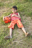 Boy resting in grass after soccer game Stock Images