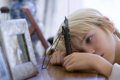 Boy (5-7) resting head on sideboard looking at picture in frame, close-up royalty free stock photo