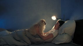 Boy resting in his bed in the evening and playing with his dog stock footage
