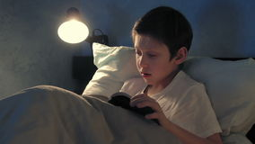 Boy resting in his bed in the evening and reading a book stock video footage