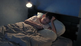 Boy resting in his bed in the evening and using his smart phone stock footage