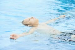 Boy resting in pool stock photography