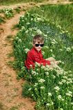 Boy resting sitting on the grass during a country walk royalty free stock photography