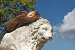 Boy resting on a stone lion Royalty Free Stock Images