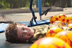 The boy is resting on the trampoline. Three year old boy is resting on the trampoline. Summertime Stock Photos