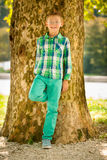 Boy resting under tree in late summer afternoon Royalty Free Stock Photo