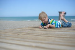 Boy resting on a wooden walkway on the beach Royalty Free Stock Photo