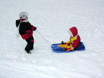 Boy ride baby on sled Royalty Free Stock Photography