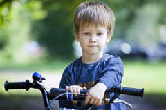 Boy ride a bicycle in city park Stock Image