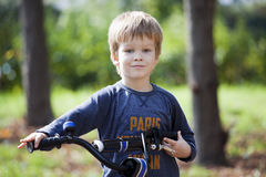 Boy ride a bicycle in city park Royalty Free Stock Images