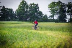 Boy ride on bike on rural landscape Royalty Free Stock Images