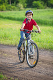 Boy ride on bike on rural road Stock Image