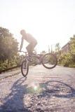 The boy ride on bike at sunrise background Stock Photography