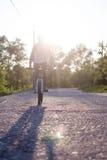 The boy ride on bike at sunrise background Stock Photo