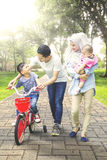 Boy rides bicycle with family at park Royalty Free Stock Images