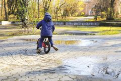 The boy rides a bicycle in puddles. The boy rides a bicycle in puddles, autumn season Royalty Free Stock Photos