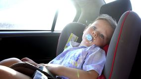 Boy rides in a child`s car seat. Summer stock footage