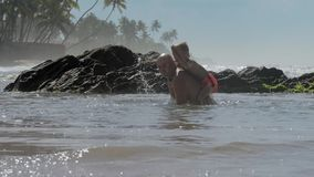 Boy rides daddy back playing in tranquil ocean bay at resort