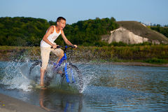 Boy rides his bike along the river Royalty Free Stock Photography