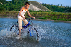 boy rides his bike along the river Royalty Free Stock Images
