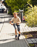 Boy rides his scooter on the paveway at a street Royalty Free Stock Photos
