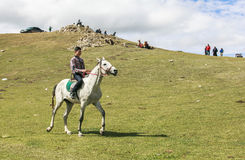Boy rides horse at Song Kul Lake in Kyrgyzstan. This photo was taken in Song kul Lake in Kyrgyzstan. The Central Asian country of Kyrgyzstan offers many stock image