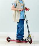 Boy rides a scooter for fun and exercise Stock Photos