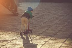 The boy rides a scooter royalty free stock image