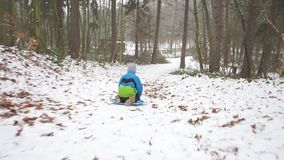Boy rides a sleigh down. A boy in a blue-green jacket, rides, sitting on a sled from a slide down in the forest among the trees stock video footage