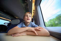 Boy rides in speed train and looks through window Stock Image