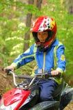 Boy riding ATV. Young boy riding ATV in a forest Stock Photo
