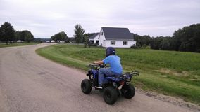 Boy riding an ATV. This is a child riding on a kids ATV wearing a helmet for safety Stock Images