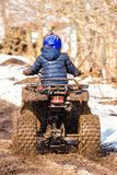 The boy is riding an ATV off-road royalty free stock images