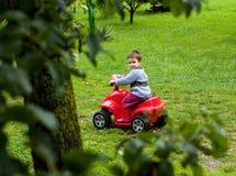 Boy riding atv toy. In garden Royalty Free Stock Photo