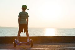 The boy is riding on a balance board.The child walks along the embankment and looks at the sunset. stock photos