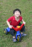 Boy riding bicycle. Happy boy with red shirt riding bicycle at the field Stock Photos