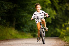 Boy riding bicycle. Little Boy riding his bicycle on a dirt road royalty free stock photo