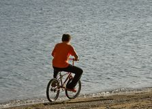 Boy riding a bicycle on a beach Royalty Free Stock Images