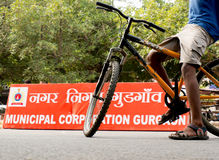 Boy riding bicycle in front of MCG board. Delhi, India; 10th Aug 2014 - Boy standing on a cycle near the Municipal corporation of Gurgaon board. The cordoned off Stock Photo