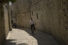 A boy riding a bicycle in the Old City of Jerusalem, and the Holy Land Royalty Free Stock Images